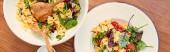 Horizontální oříznutí talíře a mísy s chutným těstovinovým salátem na dřevěném pozadí