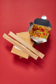 Photo top view of chopsticks in paper packaging near spicy noodles in takeaway box on red