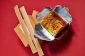 Photo top view of chopsticks in paper packaging near tasty noodles in takeaway box on red