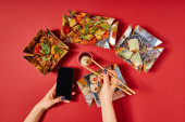 Photo top view of woman holding chopsticks with steamed bun and smartphone with blank screen near tasty chinese food in takeaway boxes on red