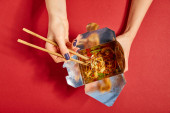 Photo top view of woman holding wooden chopsticks near tasty noodles on red