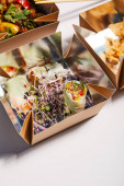 takeaway boxes with spring rolls and chinese food on white