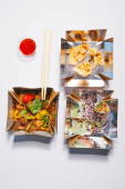 top view of takeaway boxes with chinese food near chopsticks and sauce on white