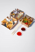 takeaway boxes with tasty and prepared chinese food near chopsticks and sauces on white