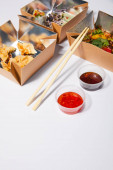 selective focus of sauces and chopsticks near takeaway boxes with prepared chinese food on white