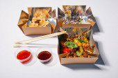 spicy sauces and chopsticks near takeaway boxes with prepared chinese food on white
