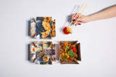 top view of woman holding chopsticks with dumpling near sauce and takeaway boxes with prepared chinese food on white