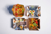 top view of tasty and spicy chinese food in takeaway boxes on white