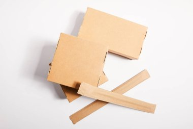 top view chopsticks in paper packaging near takeaway boxes with chinese food on white