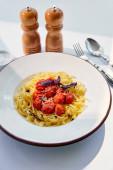 vynikající těstoviny s rajčaty servírované s příbory, solí a pepřem na bílém stole ve slunečním světle