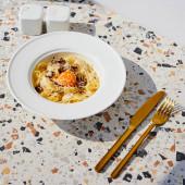 Fotografie vynikající těstoviny carbonara podávané se zlatými příbory, sůl a pepř třepačky na kamenném stole ve slunečním světle