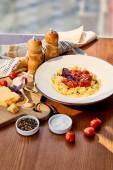 köstliche Pasta mit Tomaten auf Holztisch serviert mit Serviette, Gewürzen und Zutaten im Sonnenlicht