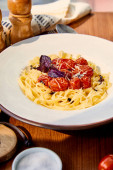 delicious pasta with tomatoes, parmesan and red basil served on wooden table in sunlight