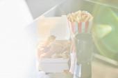 smažené kuře, hranolky a soda ve skle na skleněném stole na slunci
