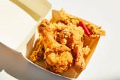 zblízka pohled na chutné a pikantní hluboce smažené kuře s chilli paprikou na bílém stole ve slunečním světle
