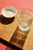 fasetovaná prázdná skleněná a bílá miska na dřevěné desce ve slunečním světle