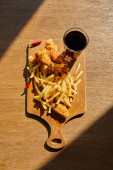 top view of spicy deep fried chicken, french fries on board with soda in glass on wooden table in sunlight