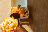 selective focus of spicy deep fried chicken, french fries and soda in glass on wooden table in sunlight