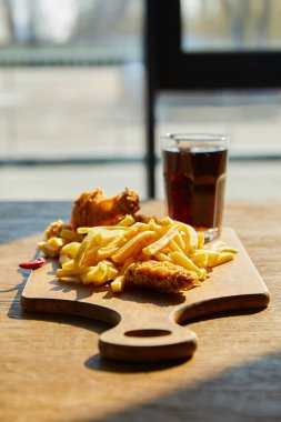 Selective focus of spicy deep fried chicken, french fries on board with soda in glass on wooden table in sunlight near window stock vector