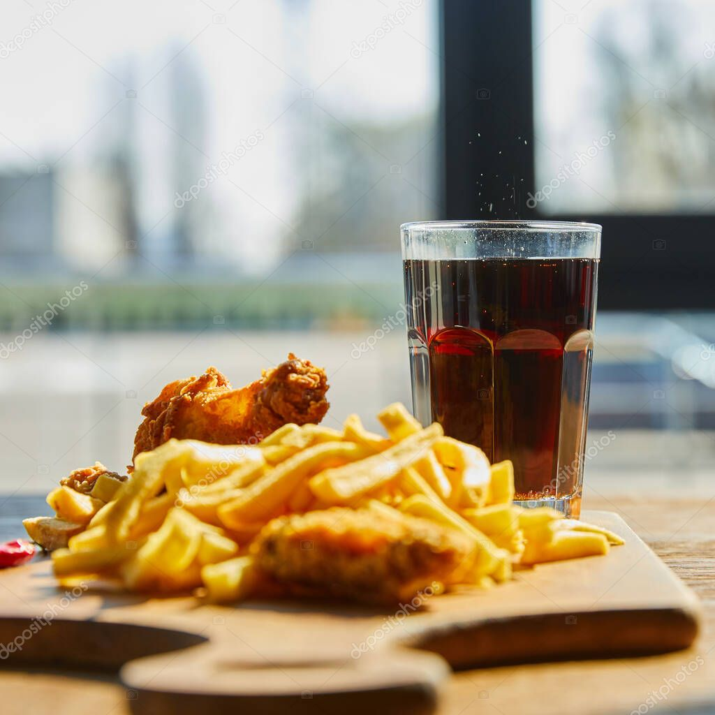 Selective focus of deep fried chicken, french fries on board with soda in glass on wooden table in sunlight near window stock vector