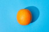 horní pohled na zralé oranžové na modrém barevném pozadí