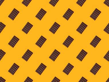 Top view of sweet dark chocolate bars on orange colorful background, seamless pattern stock vector