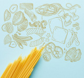 top view of raw spaghetti on blue background with food illustration