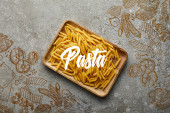 top view of raw penne on wooden board on grey textured surface with pasta illustration