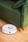 moderní automatické vysavače praní podlahy v blízkosti zelené pohovky v obývacím pokoji
