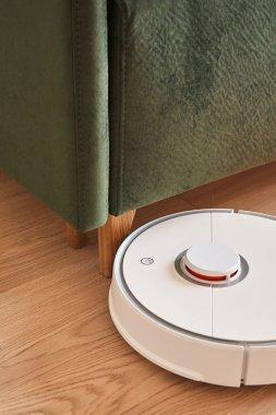 Modern robotic vacuum cleaner washing floor near green sofa stock vector