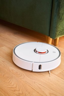 White robotic vacuum cleaner washing floor near green sofa stock vector
