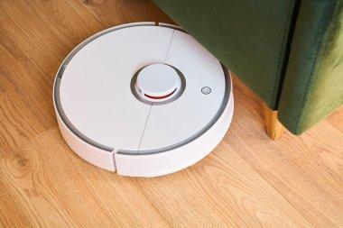 Modern automatic vacuum cleaner washing floor near green sofa stock vector