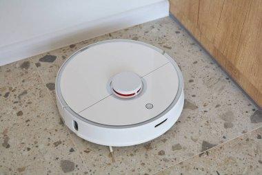 Modern robotic vacuum cleaner washing floor tiles in apartment stock vector