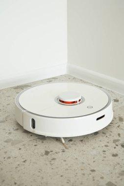 Modern robotic vacuum cleaner washing floor tiles near white walls stock vector