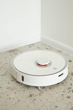 Robotic vacuum cleaner washing floor tiles near white walls stock vector