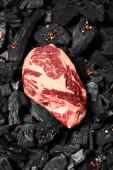 vrchní pohled na čerstvý syrový steak na černém uhlí s pepřem