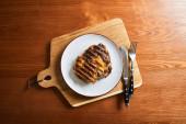 felülnézet friss grillezett steak tányéron vágódeszkán evőeszközökkel a fa asztalon