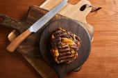 vrchní pohled na chutný grilovaný steak podávaný na dřevěných deskách s nožem