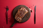 Photo top view of tasty grilled steak served on wooden board on red background with pepper and cutlery