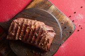 Photo top view of tasty grilled steak served on wooden board on red background with pepper and salt