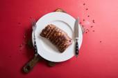 vrchní pohled na chutný grilovaný steak podávaný na desce na dřevěné desce na červeném pozadí s pepřem a solí