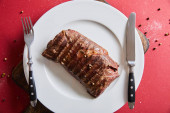 top view of tasty grilled steak served on plate on wooden board on red background with pepper and salt