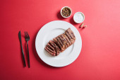 top view of tasty grilled steak served on plate with cutlery and salt and pepper in bowls on red background