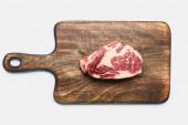 Fotografie Draufsicht auf frisches rohes Steak auf hölzernem Schneidebrett auf weißem Hintergrund