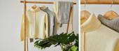 koláž béžových a šedých pletených měkkých svetrů a kalhot zavěšených na dřevěných ramínkách u zelené rostliny izolovaných na bílé