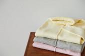 růžové, béžové a šedé pletené měkké svetry na dřevěném stole izolované na bílém