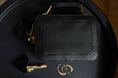 felső kilátás bőr táska közelében arany fülbevaló és rózsaszín rúzs fekete asztalon
