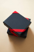 black gift boxes with red ribbons on beige background