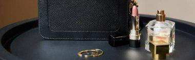 Leather handbag near golden earrings, perfume and lipstick on black table, panoramic shot stock vector