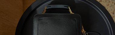 Top view of leather handbag on black table, panoramic shot stock vector